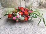 Blomsterarrangemang i båtformad skål